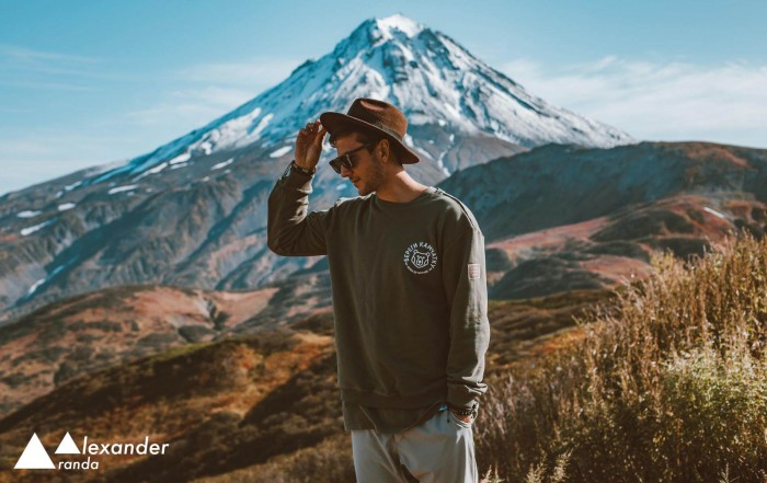 Trendy man standing in front of a mountain